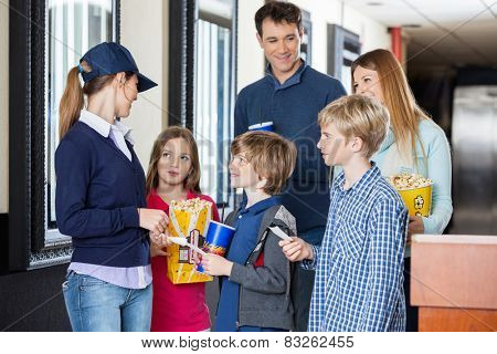 Young female worker checking movie tickets of family at cinema