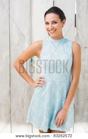 Stylish brunette smiling at camera against bleached wooden fence