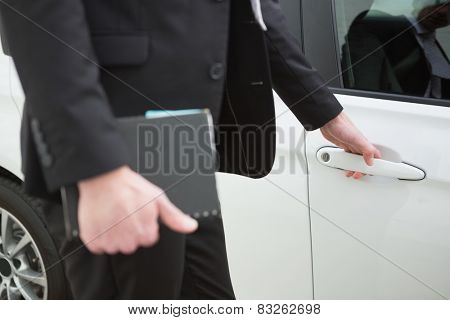 Businessman holding a car door handles in a car park