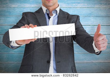 Businessman in grey suit showing card against wooden planks
