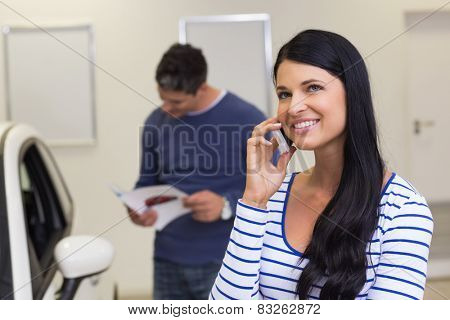 Smiling customer making a phone call at new car showroom