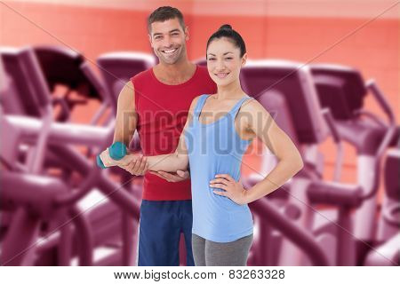 Fit woman and trainer smiling at camera against close up of treadmills in a fitness centre