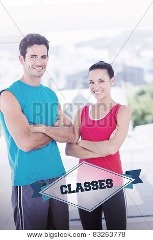 The word classes and fit couple with arms crossed in bright exercise room against badge