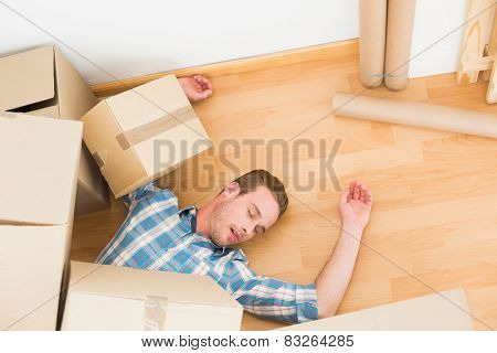 Man lying under fallen boxes at home in the living room