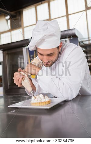 Focused baker preparing handmade cake in the kitchen of the bakery