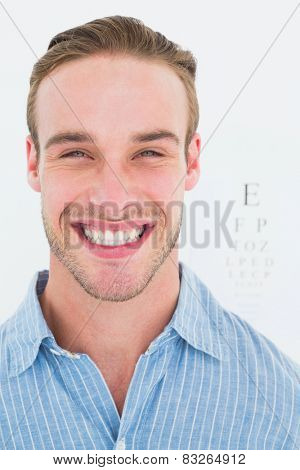 Happy handsome in shirt in front of eye test on white background