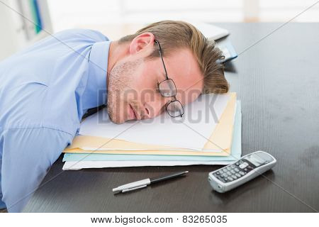 Tired businessman with stack of files on desk in his office