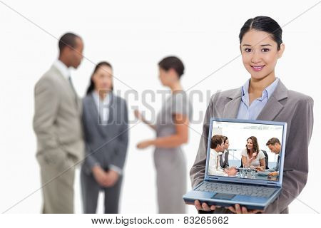Glad businesswoman talking to her team against businesswoman smiling showing a laptop screen with coworkers in the background