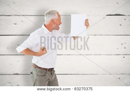 Angry man shouting at piece of paper against white wood