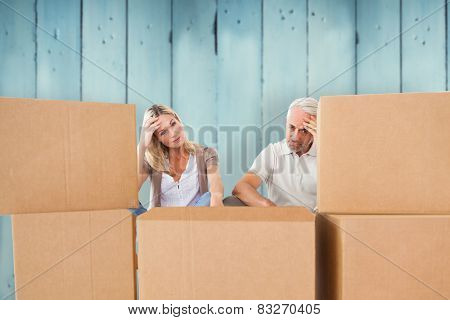 Stressed couple looking at moving boxes against wooden planks