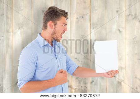 Angry man looking at page against pale wooden planks