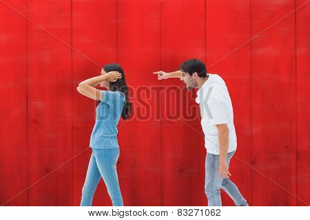 Angry boyfriend shouting at girlfriend against red wooden planks