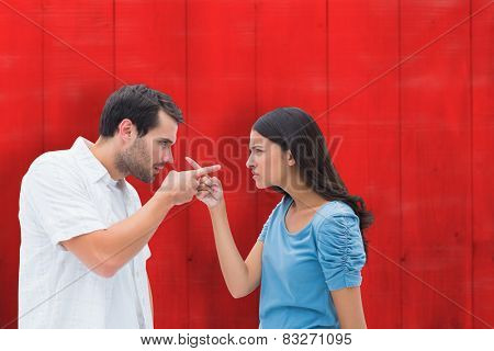 Angry couple pointing at each other against red wooden planks