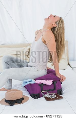 Smiling blonde closing baggage sitting on it in hotel room