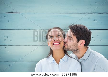 Handsome man kissing girlfriend on cheek against painted blue wooden planks
