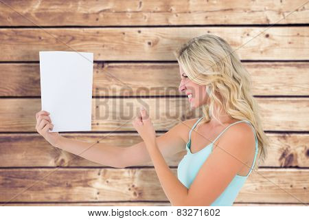 Angry blonde looking at page against wooden planks background