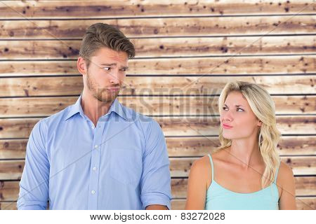 Young couple making silly faces against wooden planks background