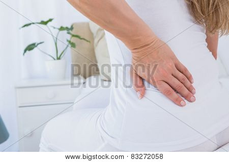 Mid section of woman getting back pain at home in the bedroom