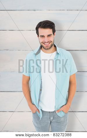 Happy casual man smiling at camera against wooden planks