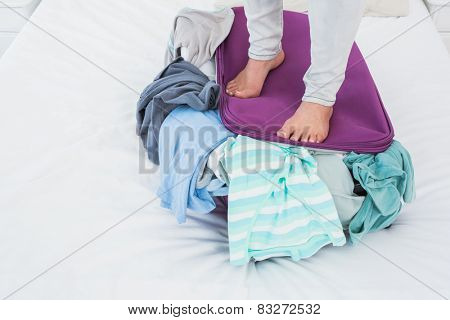 Woman standing on baggage to close it in hotel room