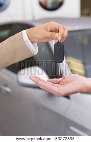 Businesswoman giving car key to happy customer at new car showroom
