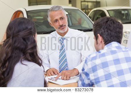 Salesperson pointing something on booklet at new car showroom