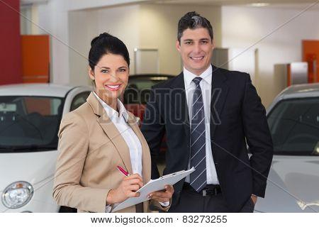 Business team smiling at camera at new car showroom