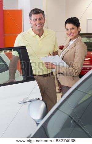 Businesswoman and her client smiling at camera at new car showroom