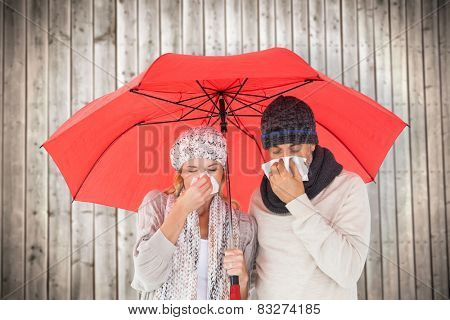 Couple in winter fashion sneezing under umbrella against wooden planks background
