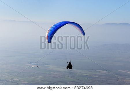 paraglider flying high above mountains