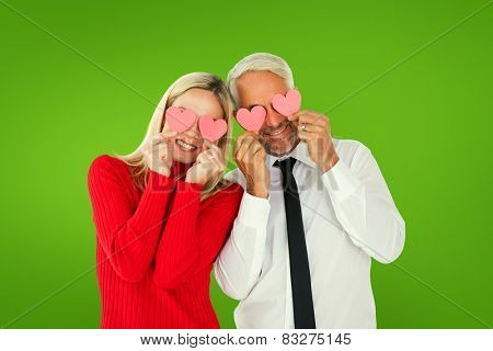 Silly couple holding hearts over their eyes against green vignette