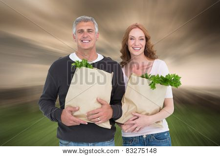Casual couple holding grocery bags against stormy sky over city