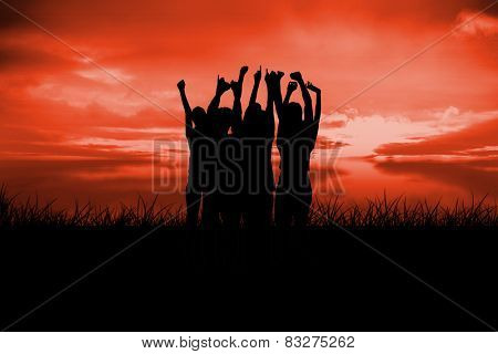 Silhouette of cheering people against red sky over grass