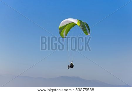 Paragliding against blue sky