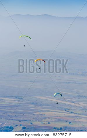 three paragliders competing above the mountain range