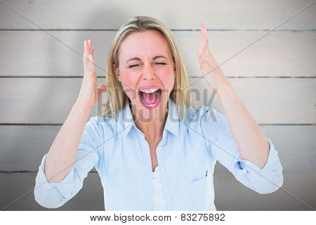 Furious blonde standing and screaming against painted blue wooden planks