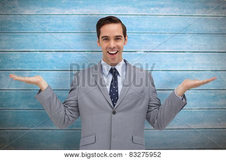 Smiling businessman presenting something with his hands against wooden planks