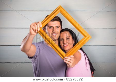 Young couple holding up frame against painted blue wooden planks