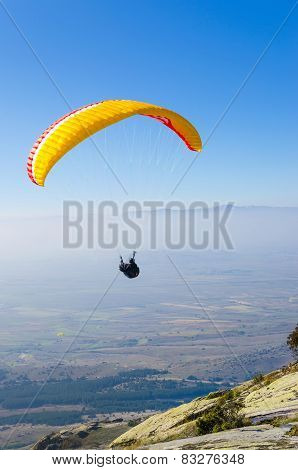 Paraglider taking off a mountain with an orange parachute
