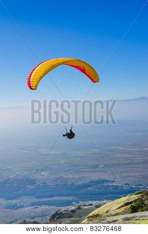 orange paraglider on the blue sky