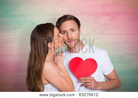 Woman kissing man as he holds heart against pink and green planks