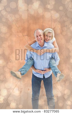 Mature man carrying his partner on his back against light glowing dots design pattern