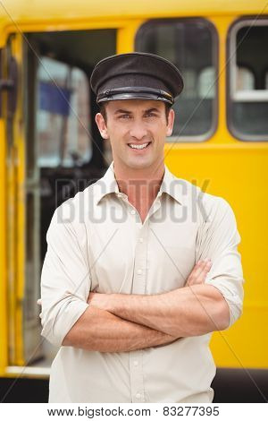 Smiling bus driver looking at camera outside the elementary school