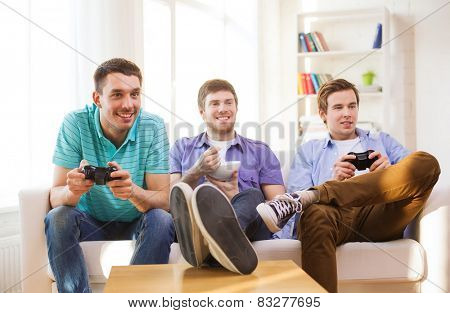 friendship, technology, games and home concept - smiling male friends playing video games at home