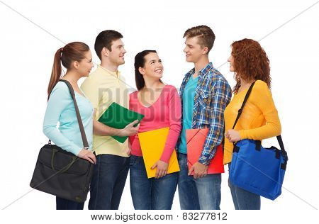 friendship, youth, education and people concept - group of smiling teenagers with folders and school bags