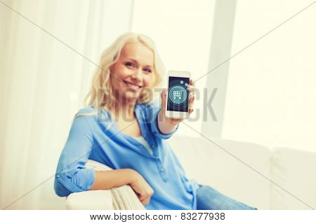 home, technology and people concept - smiling woman with showing smartphone screen with shopping trolley icon sitting on couch at home