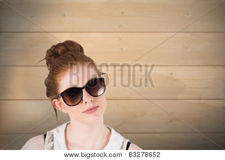 Hipster redhead wearing large sunglasses against bleached wooden planks background