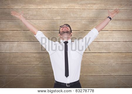 Cheering businessman with his arms raised up against wooden surface with planks