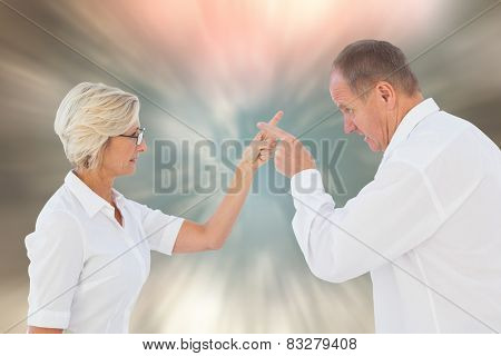 Angry older couple arguing with each other against blurred christmas background