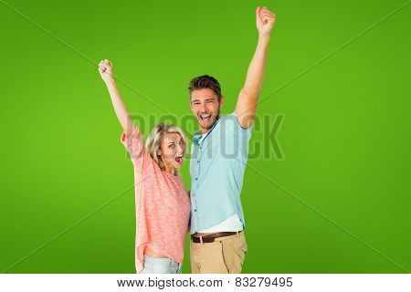 Attractive couple smiling and cheering against green vignette